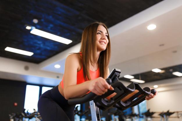 En kvinde cykler på en motionscykel